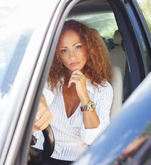 Beautiful middle-aged redhead woman behind steering wheel