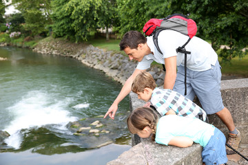 Man showing fishes from river to kids