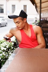 Stylish young man in  cap sitting behind table in cafe