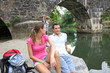 Couple relaxing by bridge, kids in background
