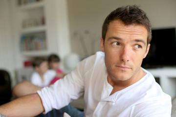 Portrait of man sitting in sofa, kids in background