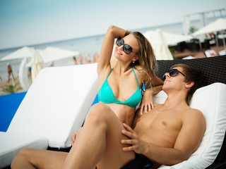 Sexy young couple relaxing on a beach bed