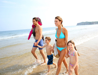 Family in summer vacation walking on the beach