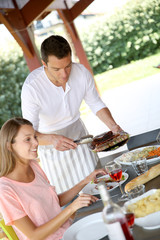 Man serving grilled food to family