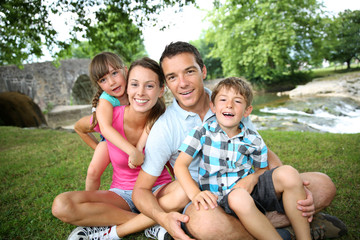 Family relaxing by river in countryside