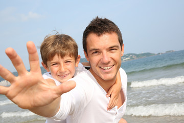 Man holding son on his back at the beach