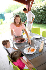 Mom serving grilled food to children