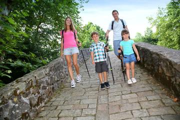 Family on a rambling journey crossing roman bridge