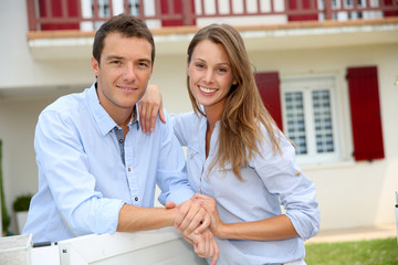 Cheerful couple standing in front of new home