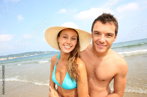 Cheerful young couple standing on the beach