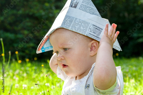 Baby with Paper on the summer meadow