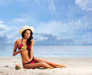 A young brunette woman eating grapes on the beach