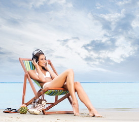 A young brunette woman listening to the music on the beach