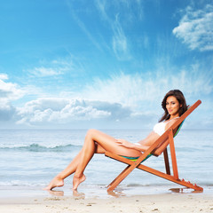 A young brunette caucasian woman relaxing on the beach