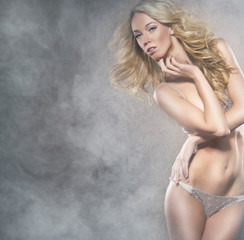 A young blond woman in lingerie posing on a foggy background