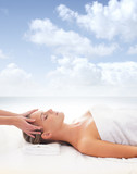 A young woman relaxing on a spa massage on a sky background