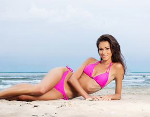A young brunette woman in pink bikini relaxing on the beach