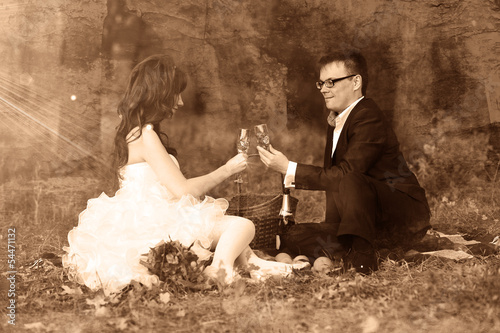 Russia newlyweds couple bride, and groom sitting on green grass,