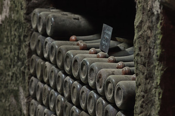 Row of old dusty wine bottles in an ancient wine cellar