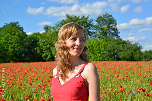 The young woman smiles in a poppy field