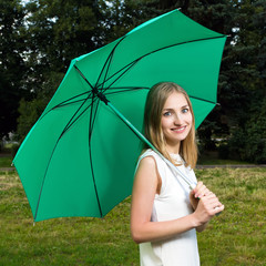 Beautiful smiling girl holding a green umbrella in a park
