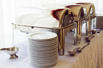 metal kitchen equipments and plates on the table