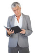 Concentrated businesswoman reading notepad
