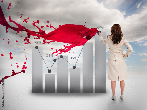 Creative businesswoman drawing a chart next to red paint splash