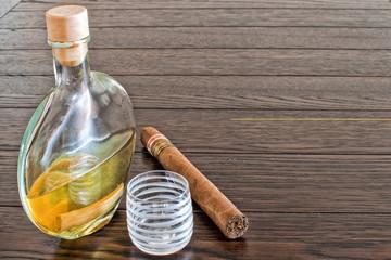 bottiglia di grappa con sigaro e bicchiere