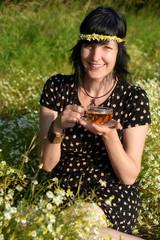 Frau im Kamillefeld trinkt Tee