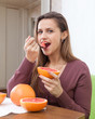 girl eats grapefruit with spoon