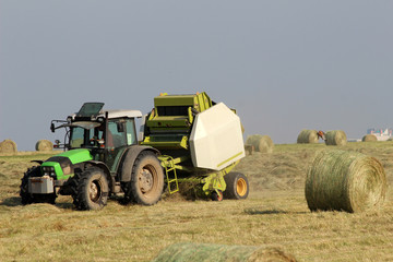 Tractor collecting haystack in the field