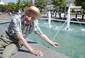 Senior man is searching refreshment by the fountain.