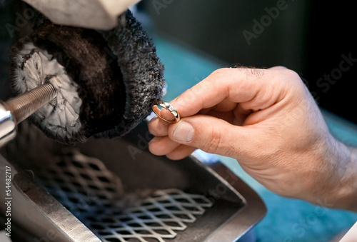 Male hand is polishing a wedding ring