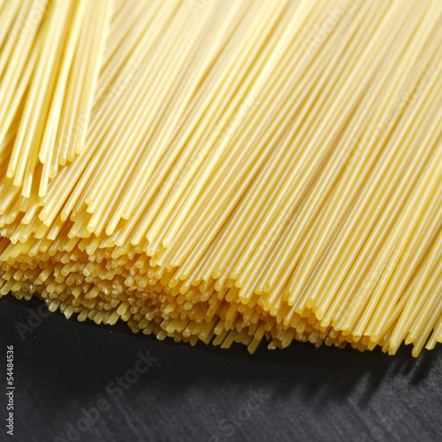 Raw pasta on black table