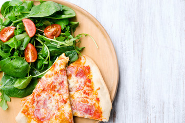 Pizza with salad dinner on rustic background