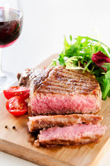 Grilled rib eye steak served with healthy salad