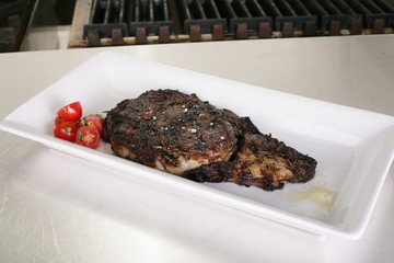 Rib-eye steak resting on the plate in the kitchen ready to serve
