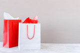 Presents on the table, red and white paper shopping bags