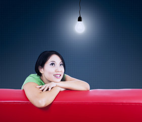 Asian female looking at lamp on red sofa