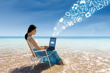Asian female using laptop at beach