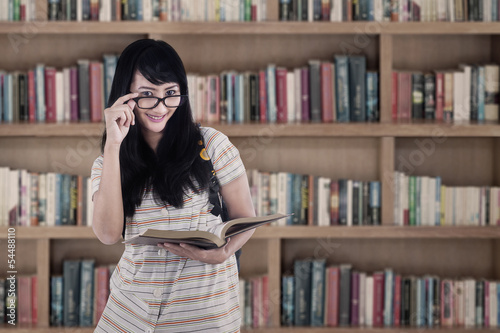 Asian female holding book at library
