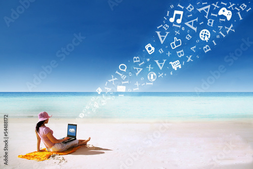 Asian woman using laptop at beach