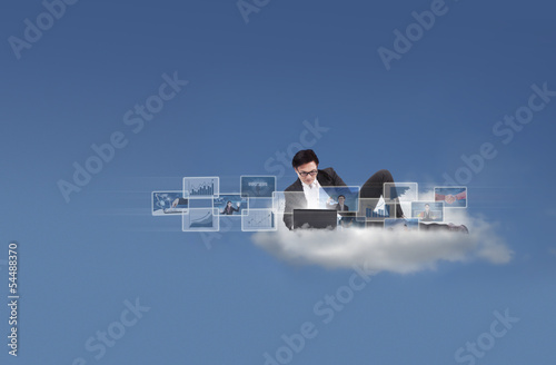 Businessman on cloud using internet