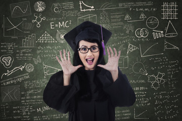 Excited female graduate and written board