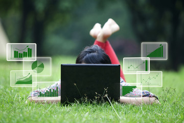 Female lying on grass with laptop and bar chart