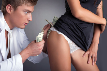 Young man puts money into stripper's panties