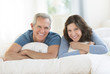 Portrait Of Happy Couple Lying Together In Bed