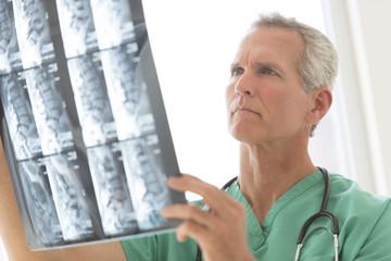 Surgeon Examining X-Ray Report
