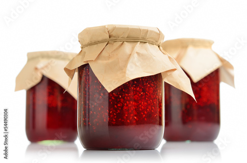 Three jars of raspberry jam on white background